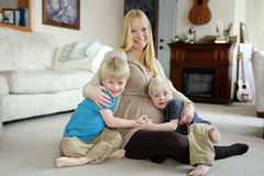Happy Pregnant Mother and Her Two Young Children at Home Royalty Free Stock Photo