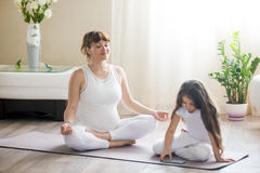 Happy pregnant mother and kid girl spending time together at home. Portrait of young happy pregnant yoga mom spending time with her little daughter, meditating stock photos