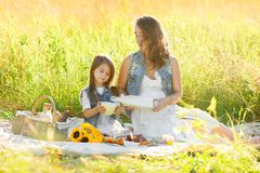 Concept of maternity - pregnant mother and little daughter on a sunny summer day, sit on the grass and drink milk royalty free stock photos