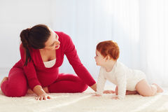 Happy pregnant mother and toddler baby playing at home stock images