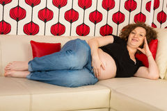 Happy pregnant relaxing on sofa Stock Image