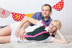 Happy pregnant wife and husband lie on carpet Royalty Free Stock Photo