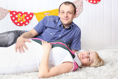 Happy pregnant wife and husband lie on carpet Stock Photos