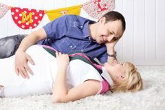 Happy pregnant wife and husband lie on carpet Royalty Free Stock Photos