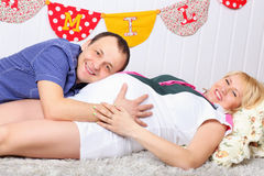 Happy pregnant wife and husband lie on carpet Stock Image