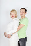 Happy pregnant wife in white and husband hold belly Stock Image