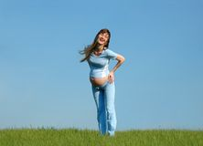 Happy  pregnant woman. Smiling pregnant woman on blue sky background Royalty Free Stock Photography
