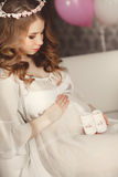 Happy pregnant woman admires the children's shoes. Royalty Free Stock Photos