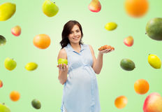 Happy pregnant woman with apple and croissant Royalty Free Stock Photo
