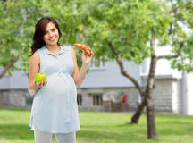 Happy pregnant woman with apple and croissant Stock Image