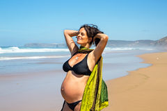 Happy pregnant woman  at the atlantic ocean. Happy pregnant woman on the beach at the atlantic ocean Royalty Free Stock Photos