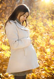 Happy pregnant woman in the autumn park Stock Photos