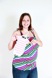 Happy pregnant woman with baby clothes Stock Photo
