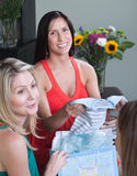Happy Pregnant Woman With Baby Clothes. Smiling pregnant women shows baby clothes to her friends Royalty Free Stock Image