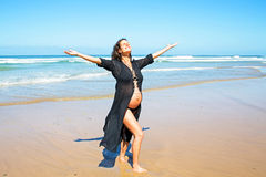 Happy pregnant woman on the beach Stock Images