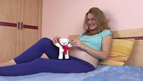 Happy pregnant woman on bed and play with white teddy bear toy stock video footage