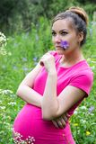 Happy pregnant woman with big belly and flower rest Royalty Free Stock Image