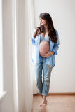 Happy pregnant woman with big tummy at home Stock Photos