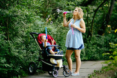 Happy pregnant woman blowing soap bubbles with child Stock Photography