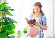 Happy pregnant woman with book at window Royalty Free Stock Images