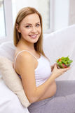 Happy pregnant woman with bowl of salad Stock Photo