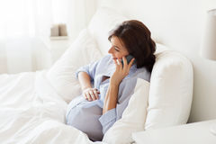 Happy pregnant woman calling on smartphone at home Royalty Free Stock Image