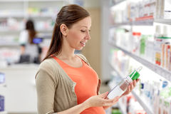 Happy pregnant woman choosing lotion at pharmacy. Pregnancy, medicine, pharmaceutics, health care and people concept - happy pregnant woman choosing anti stretch Royalty Free Stock Images