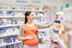 Happy pregnant woman choosing medicine at pharmacy Stock Photos