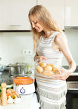 Happy  pregnant woman cooking fresh vegetables with electric ste Royalty Free Stock Photos
