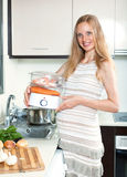 Happy pregnant woman cooking Stock Photography