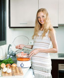 Happy pregnant woman cooking Stock Photos