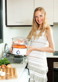 Happy  pregnant woman cooking vegetables Stock Photos
