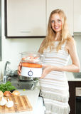 Happy  pregnant woman cooking vegetables and salmon in electric Stock Photos