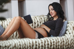 Happy pregnant woman on couch at home, using a digital tablet Royalty Free Stock Image