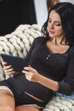 Happy pregnant woman on couch at home, using a digital tablet Stock Photography