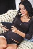 Happy pregnant woman on couch at home, using a digital tablet Stock Photos