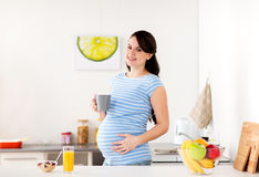 Happy pregnant woman with cup at home kitchen Stock Image