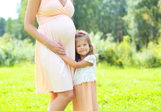 Happy pregnant woman, cute little child daughter hugging mother Stock Photo