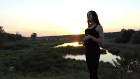 Happy pregnant woman dance at sunset. Beautiful action in the real time stock video footage