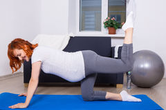Happy pregnant woman doing stretching exercises in living room Royalty Free Stock Photography