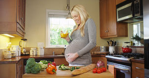 Happy Pregnant woman drinking juice Royalty Free Stock Photos