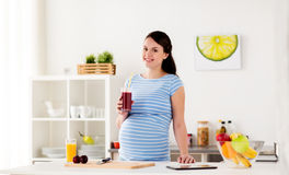 Happy pregnant woman drinking juice at home Royalty Free Stock Photography
