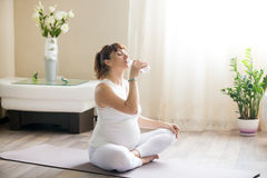 Happy pregnant woman drinking natural water after working out stock images