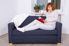 Happy pregnant woman drinking tea and reading book at home Stock Photography