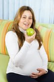 Happy pregnant woman eating a green apple Royalty Free Stock Image
