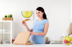 Happy pregnant woman eating pizza at home kitchen Royalty Free Stock Photography