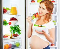 Happy pregnant woman eating salad near refrigerator royalty free stock image