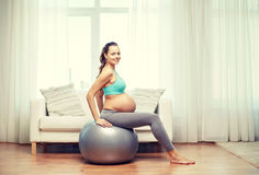 Happy pregnant woman exercising on fitball at home Stock Photos