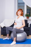 Happy pregnant woman exercising on fitball at home Stock Photo