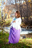 Happy pregnant woman in fall nature. By a river Stock Image